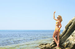 Blonde posing leaning against rock near ocean coast Royalty Free Stock Photography