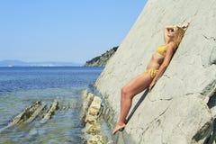 Blonde posing leaning against rock near ocean coast Stock Photo