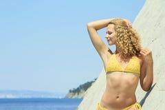 Blonde posing leaning against rock near ocean coast Royalty Free Stock Image