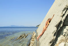 Blonde posing leaning against rock near ocean coast Stock Photos