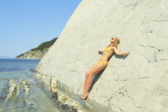 Blonde posing leaning against rock near ocean coast Stock Photography