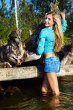 Blonde posing near flotsam. Young beautiful blonde outdoors, standing in the water near flotsam Stock Photos