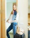 Blonde positive Frau, die Tür schaut Lizenzfreie Stockbilder