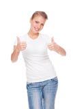 Blonde positivo joven que muestra los pulgares para arriba Foto de archivo libre de regalías