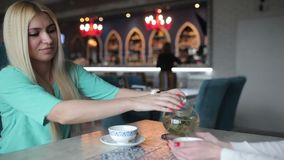 The blonde pours a cup of tea from a teapot. Woman pours green tea in white cup. Young woman pouring tea into cups made of transparent teapot stock video