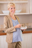 Blonde pregnancy smiling at camera and eating Royalty Free Stock Photography