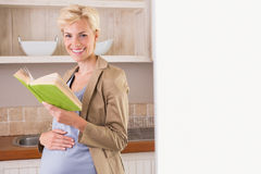 Blonde pregnancy smiling at camera and take a book Stock Photos