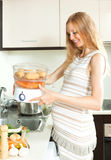 Blonde  pregnant housewife cooking vegetables  with electric ste Stock Photos