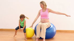Blonde pregnant woman sitting on exercise ball with her little girl stock video