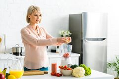 Pregnant young woman preparing food in kitchen