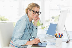 Blonde pretty designer looking at the camera using digitizer Stock Image