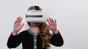 Blonde pretty girl using VR moving around. Girl revolves around itself in an imaginary indoor stock video