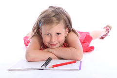 Blonde primary school girl with pencil and paper Royalty Free Stock Image