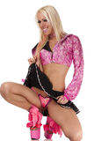 Blonde pulls up her skirt. Coquettish blonde in pink pulls up her skirt Royalty Free Stock Photography
