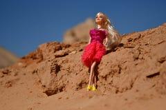 Blonde Puppen spielen im Sand und gehen zusammen in einen felsigen Bereich Stockbild