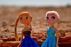Blonde Puppen spielen im Sand und gehen zusammen in einen felsigen Bereich Lizenzfreies Stockfoto