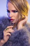 Blonde in purple fur coat with long hair Stock Image