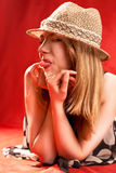 Blonde put out tongue. Lying in beach hat stock photography