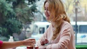 Blonde que disfruta de té caliente y de negociaciones con el amigo en café metrajes