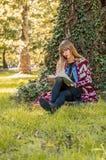 blonde que goza del libro en el parque Imágenes de archivo libres de regalías