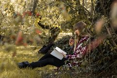 blonde que goza del libro en el parque Fotografía de archivo libre de regalías