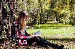 blonde que goza del libro en el parque Fotos de archivo libres de regalías