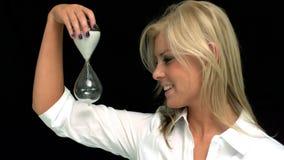 Blonde que mira un reloj de arena metrajes