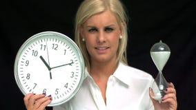 Blonde que muestra un reloj de arena y un reloj almacen de metraje de vídeo