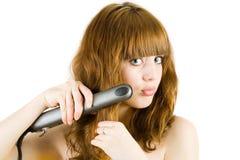 Blonde que usa a la enderezadora del pelo Fotos de archivo libres de regalías