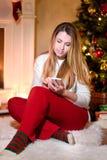 Blonde que usa su smartphone que se sienta en una sala de estar foto de archivo