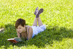 Blonde reading at park Stock Image
