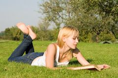 Blonde Reads Book In The Park Stock Photo