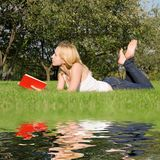 Blonde Reads Book In The Park Royalty Free Stock Photos