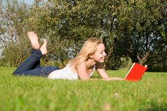 Blonde reads book in the park Royalty Free Stock Photo