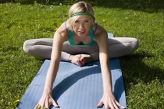 Blonde real girl doing yoga in green park on grass Royalty Free Stock Image
