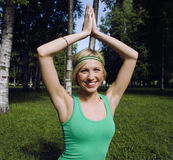 Blonde real girl doing yoga in green park on grass Stock Image