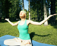 Blonde real girl doing yoga in green park on grass Stock Photos