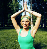 Blonde real girl doing yoga in green park on grass Stock Photo