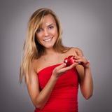 Blonde recht junge Frau mit dem Valentinsgruß anwesend in den Händen im Re Stockfoto