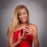 Blonde recht junge Frau mit dem Valentinsgruß anwesend in den Händen im Re Lizenzfreie Stockbilder