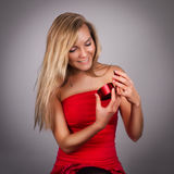 Blonde recht junge Frau mit Valentinsgrüßen stellen sich in den Händen im Re dar Lizenzfreie Stockfotos