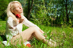 Blonde with red apple. Women with red apple. Outdoor Stock Image