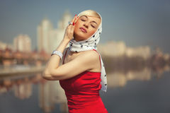 Blonde in a red dress closed her eyes Stock Image