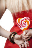 Blonde in a red dress holds lollipop Stock Images