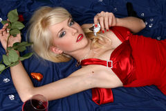 Blonde in a red dress with rose in hand Royalty Free Stock Image