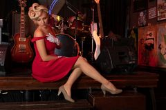 Sexy blonde sitting on a stage in front of musical instruments stock photography