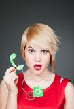 Blonde in red dress with small model of retro phone Stock Photo