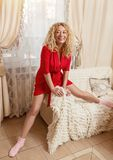 Blonde in red home dress and socks on couch. Smiling blonde with curly hair sitting on couch Stock Image