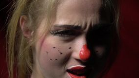 A creepy girl clown stands quietly and begins to grimace stock video