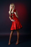 Blonde in a red satiny dress Stock Photos